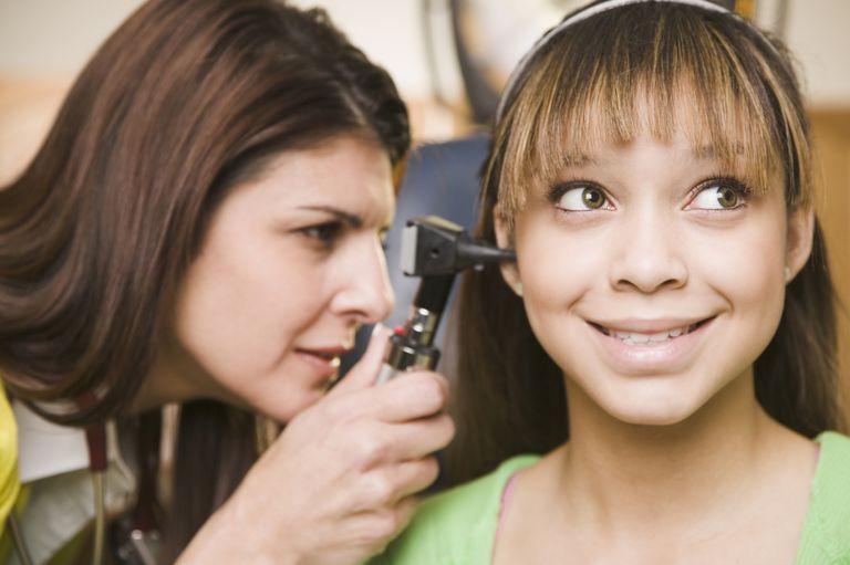 Doctor examinando las orejas de una adolescente