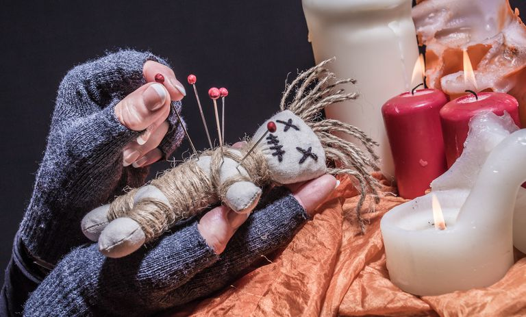 Cropped Hands Inserting Straight Pin In Voodoo Doll