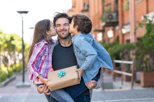 Amoroso hijo e hija besando a papá en la mejilla mientras los lleva a ambos, junto con un regalo para el día del padre