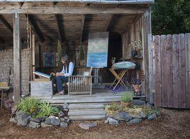 fine artist in outdoor studio working on painting