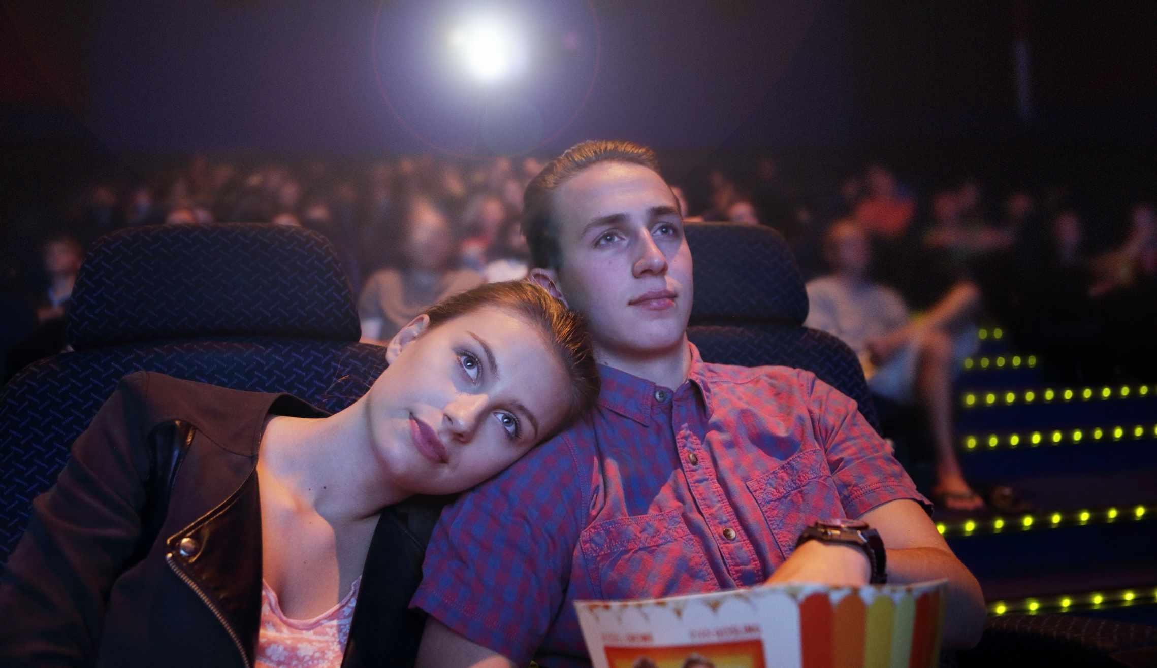 Una pareja ve una película y come palomitas en el cine