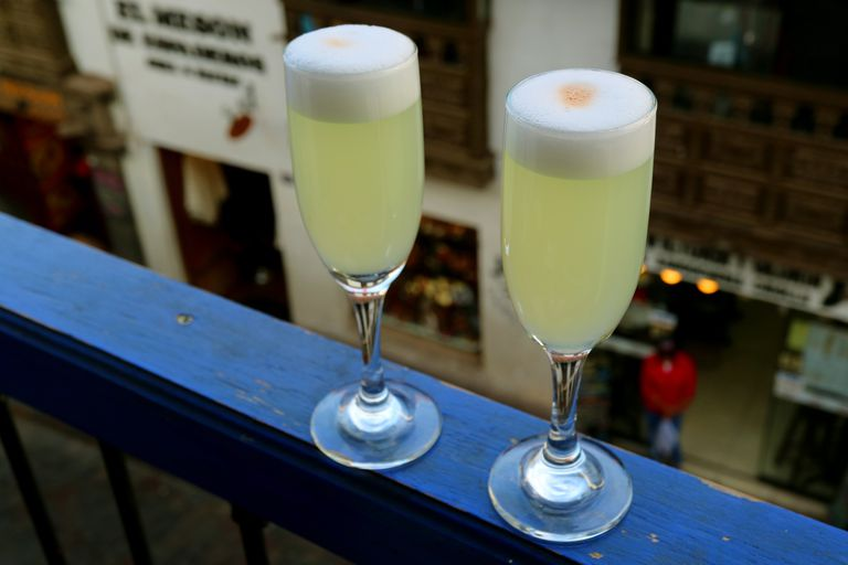 Two Glasses of Peruvian Pisco Sour with the Historic Building of Cusco Old City in Background, Peru, South America