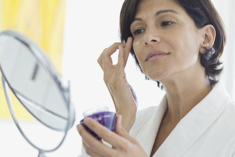 Mujer aplicar crema de ojos