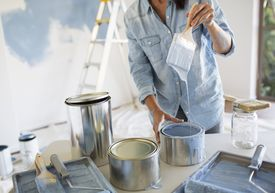 Una mujer sostiene pincel con pintura azul