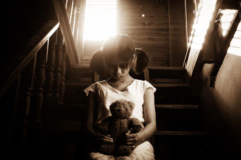 Niña en vestido blanco sentado en la escalera en casa abandonada