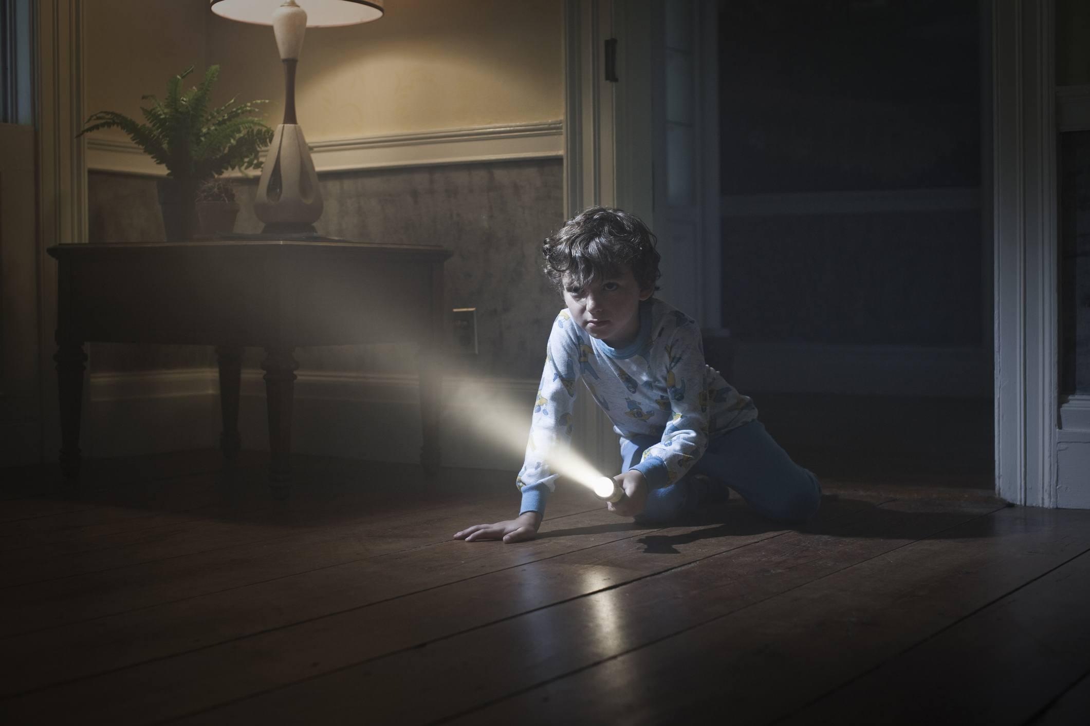 Niño en pijama en el piso con linterna