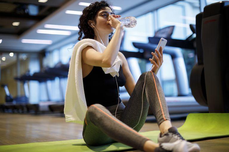 Mujer joven bebiendo una botella de agua después de hacer ejercicio en el gimnasio