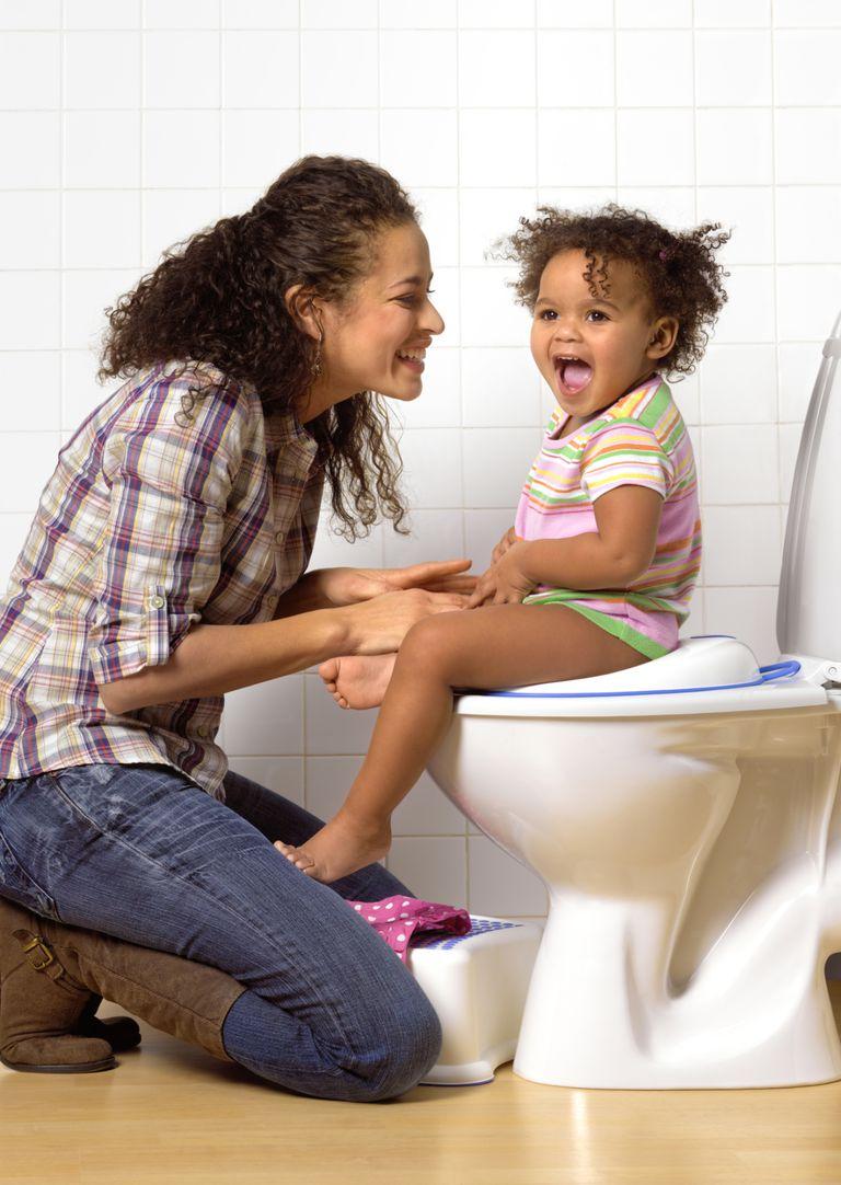 Niña latina sentada en el wc