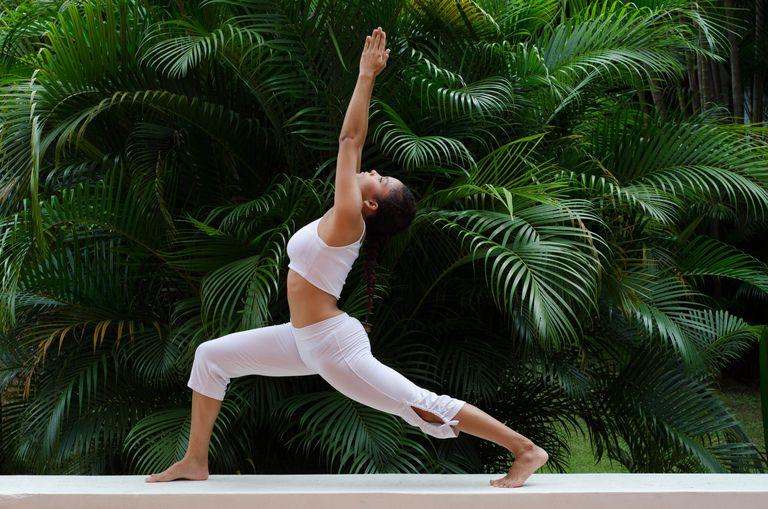 Una mujer haciendo una pose de yoga en un jardín