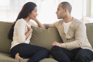 Una joven pareja sentada en un sofá y hablando
