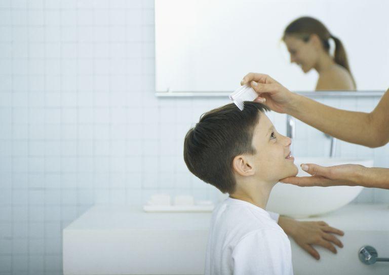 Madre peinando a hijo con espejo de fondo