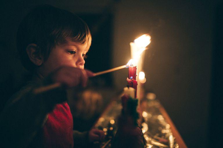 niño enciende una fila de velas para la temporada de Adviento