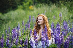 Serena joven meditando con las manos juntas entre flores silvestres púrpuras