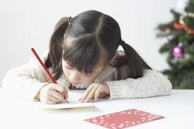 Niña escribiendo tarjeta de navidad