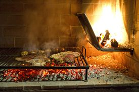 Meat cooking on traditional argentine grill with fire and coals in Chacras De Coria Mendoza, Argentina
