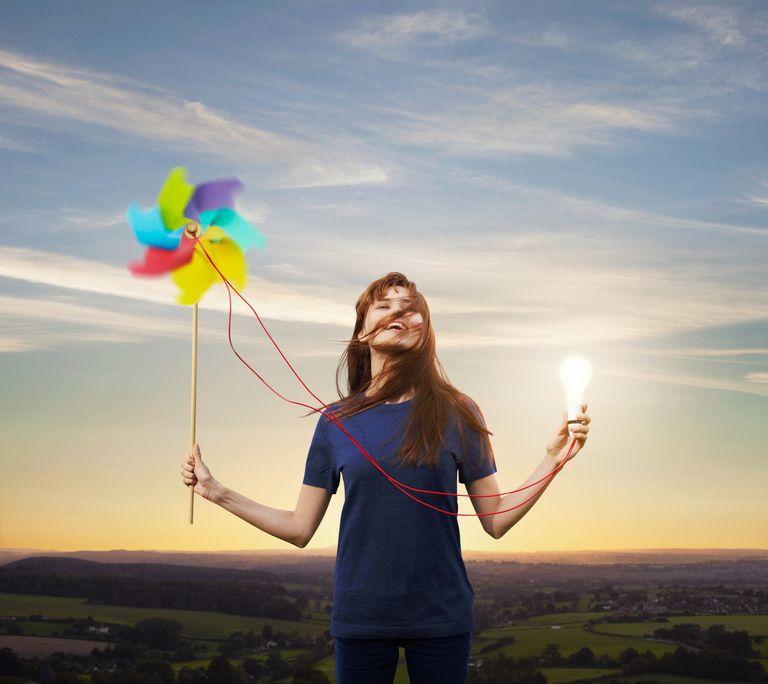 Mujer con una bombilla impulsada por una turbina de viento