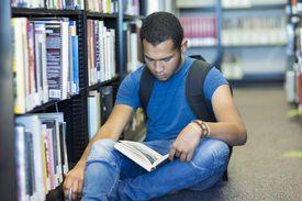 Niño leyendo un libro en la biblioteca