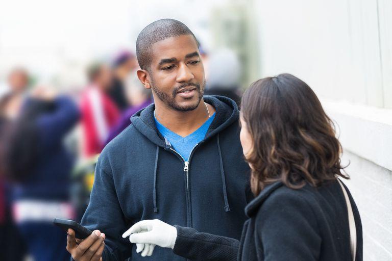 Un hombre que mantiene su teléfono celular alejado de su novia celosa