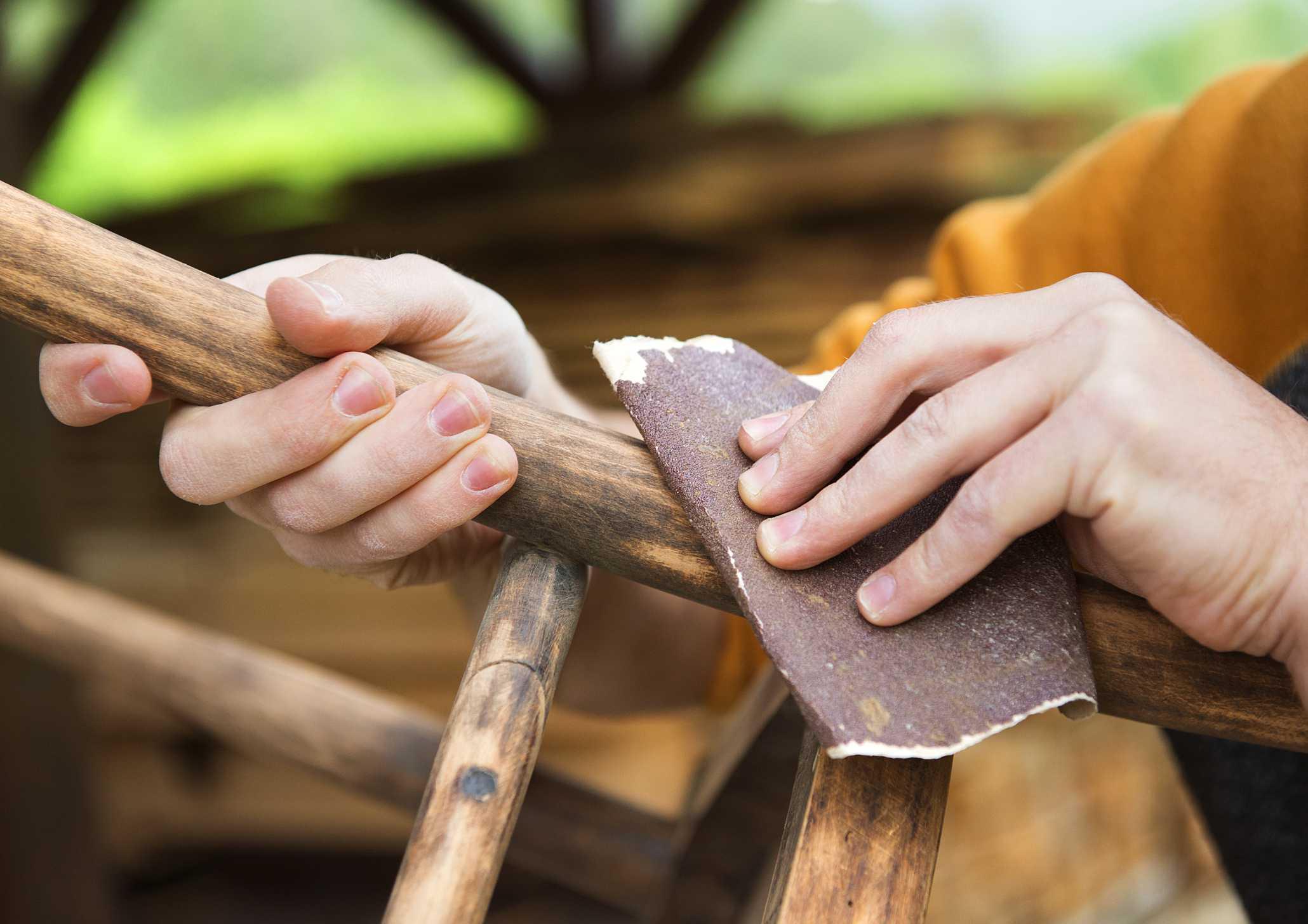 Quitar la pintura de la silla antigua con papel de lija