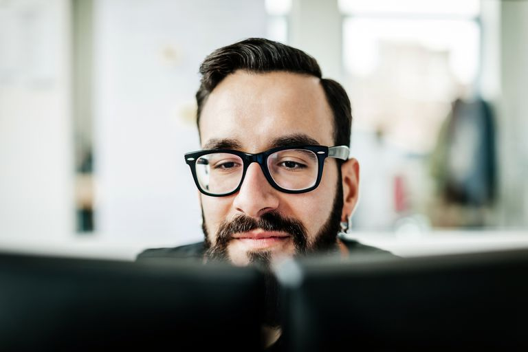 Hombre mirando los monitores de su computadora