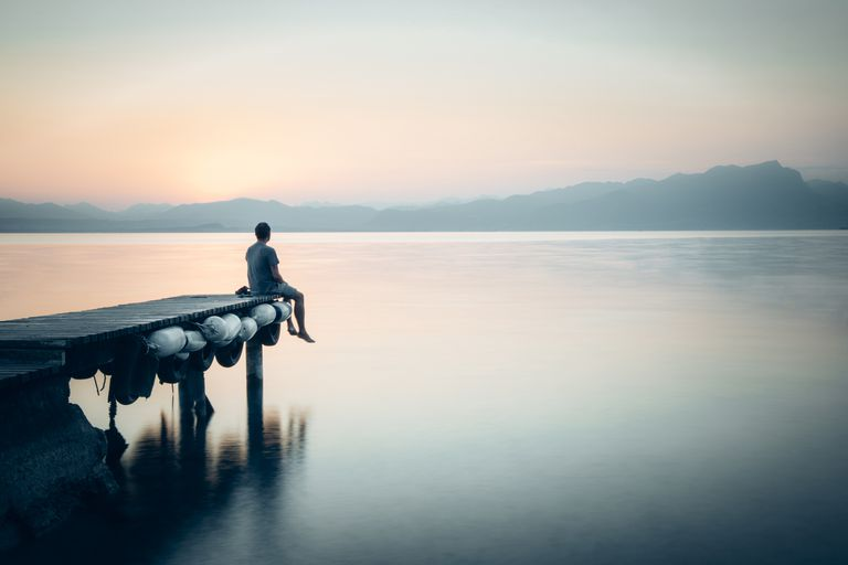 Person seating by the water at sunrise
