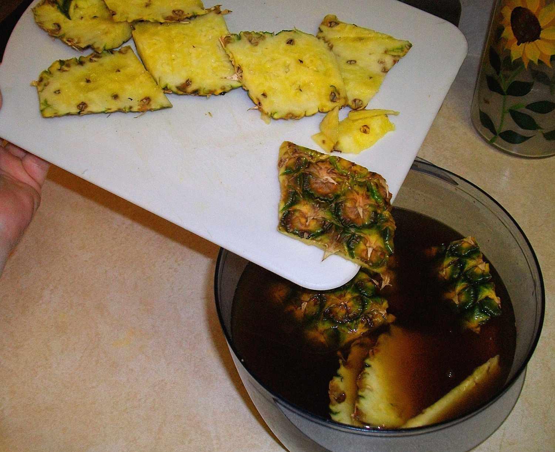 Se introduce la cáscara de piña al agua con piloncillo para elaborar tepache.
