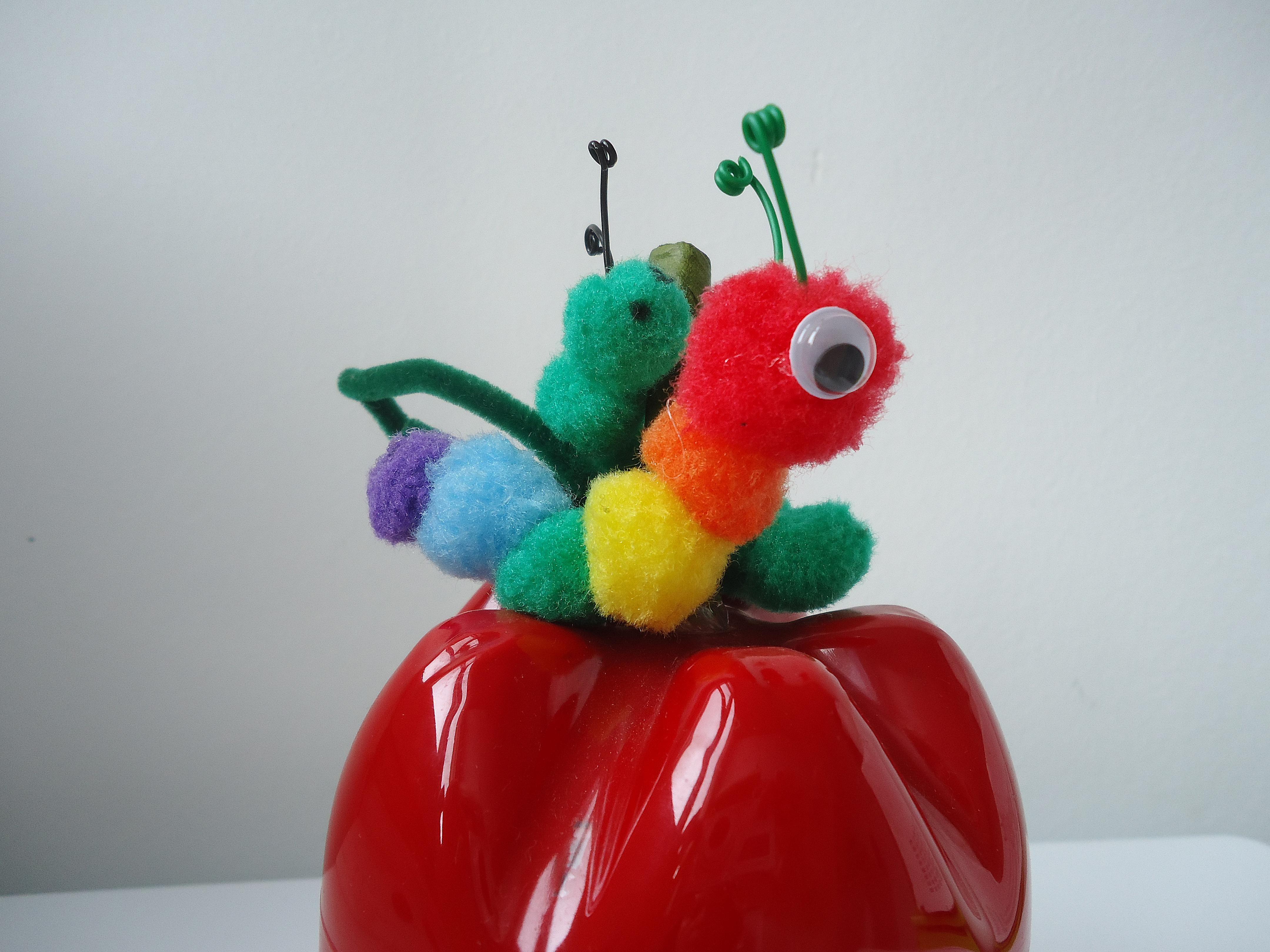caja de manzana con gusano pompons