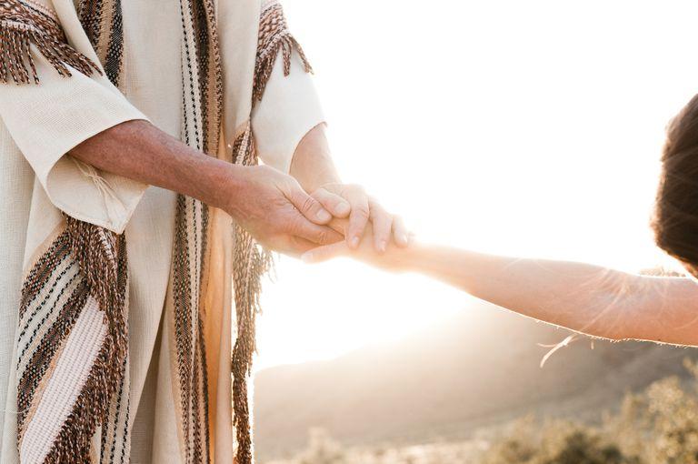 Jesús sosteniendo la mano de una mujer