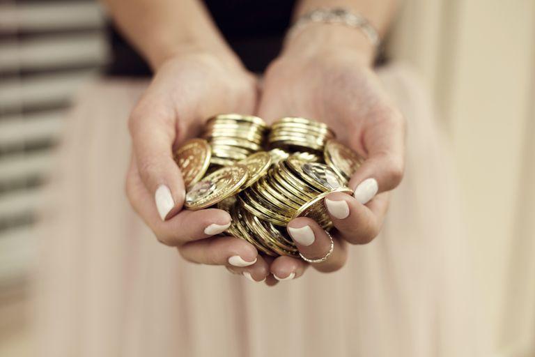 Manos de mujer sosteniendo monedas de oro