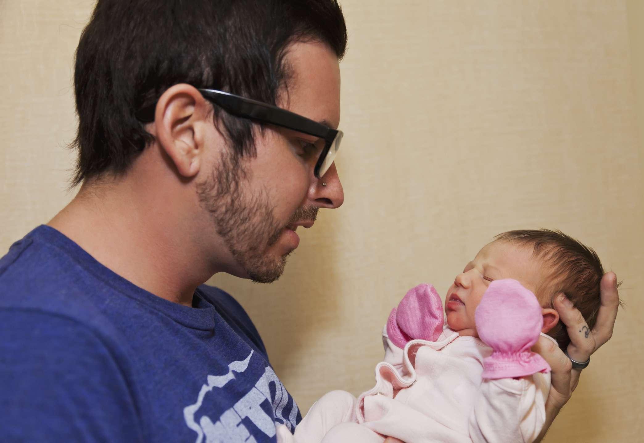 Padre sosteniendo a su hija recién nacida