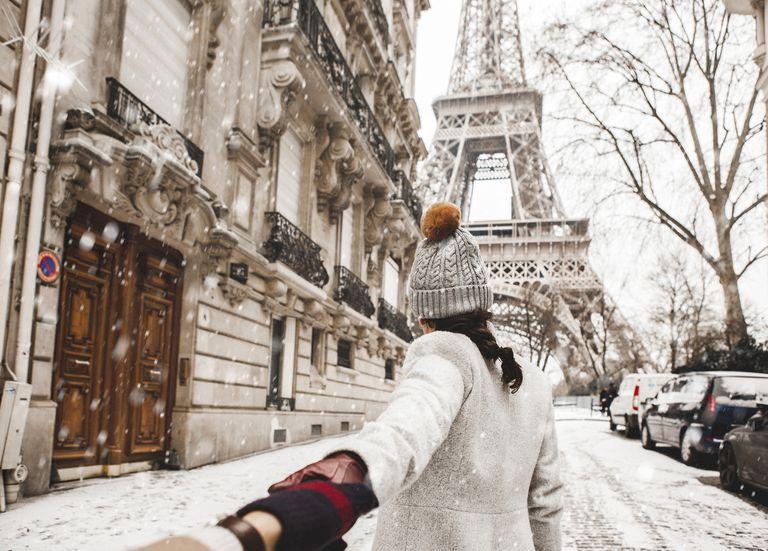 Mujer caminando hacia la torre eiffel en la nieve