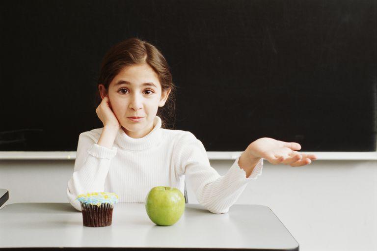 Chica (10-12) sentado en el escritorio con manzana y magdalena