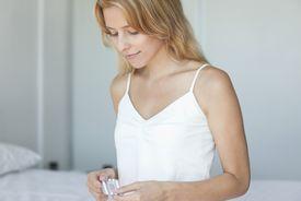 Mujer sosteniendo píldoras de control de natalidad