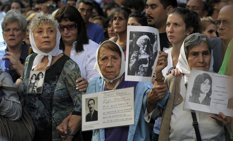 Members of the Human Rights organization Madres de Plaza de Mayo Linea Fundadora, and other demonstrators, hold portraits of people who went missing in the 1976-1983 military dictatorship