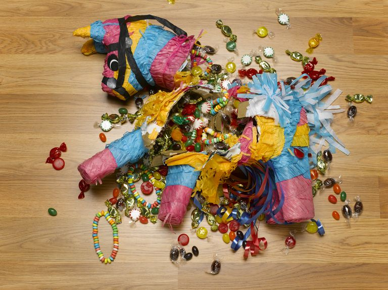 Smashed donkey pinata on floor with candy