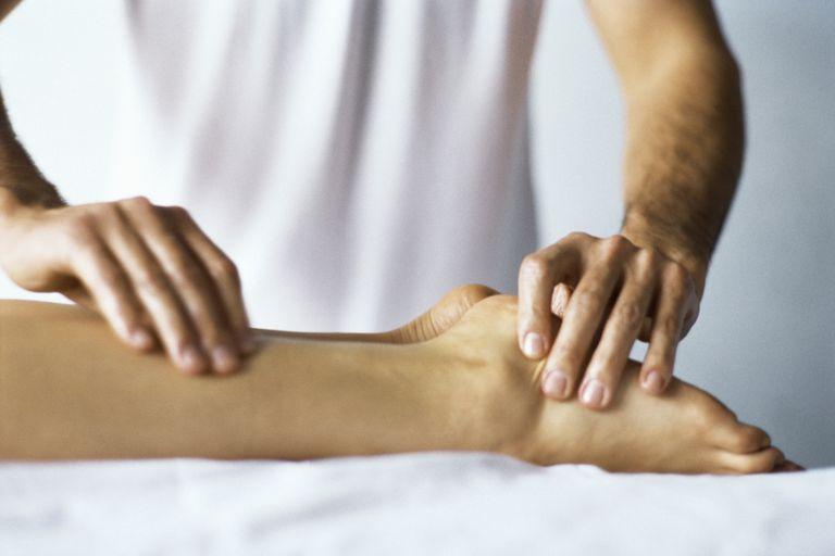 Practicante de Shiatsu haciendo presión en meridianos de la pierna