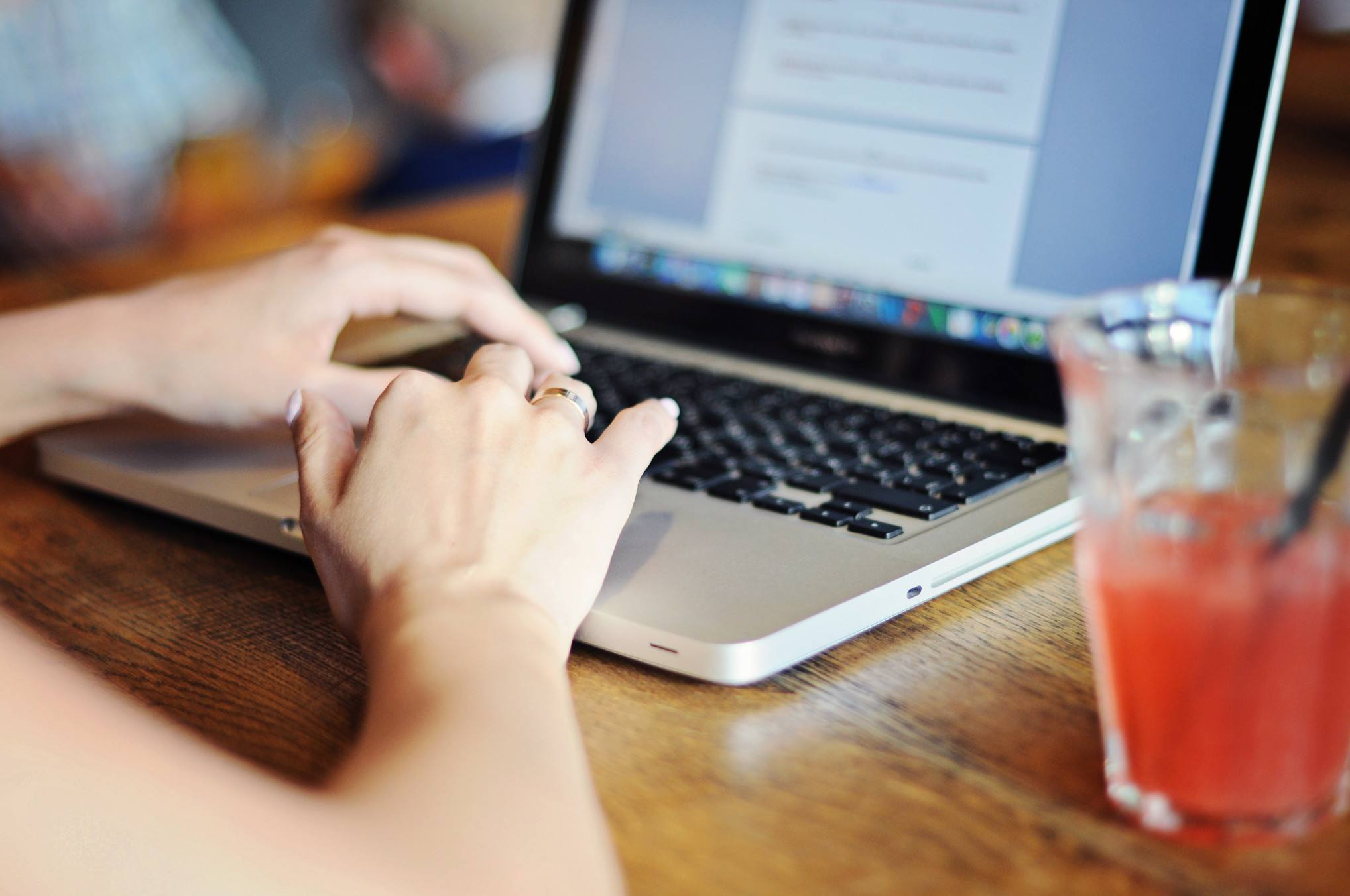 A woman's hands on a laptop with a drink sitting on the table next to it.