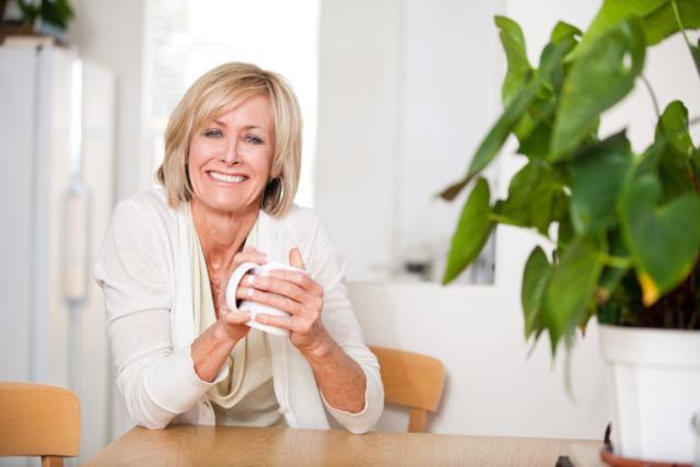 Mujer en la menopausia tomando tisana de plantas medicinales