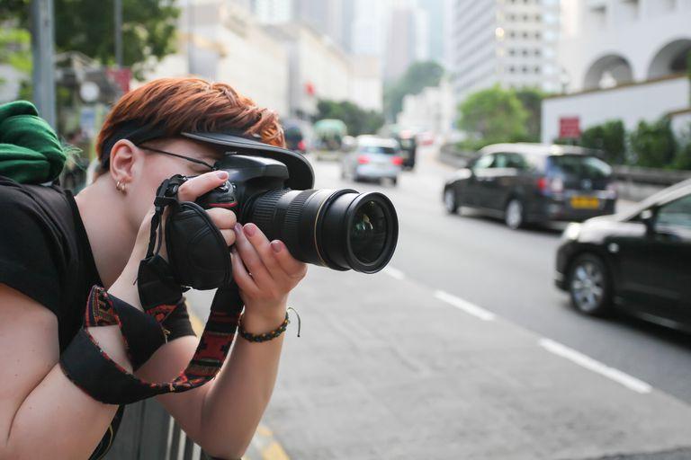 Mujer tomando una foto con una DSLR en la ciudad