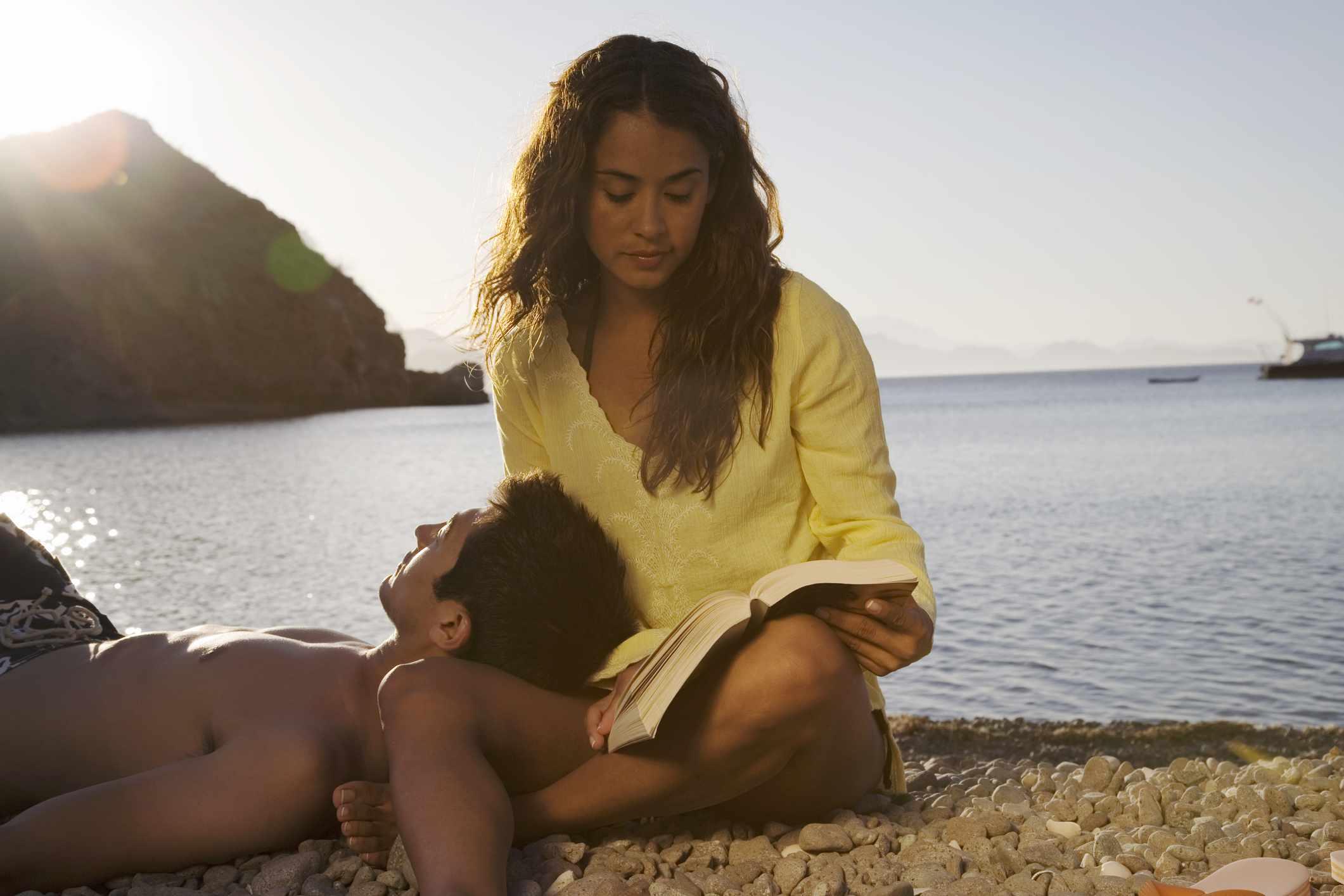 Una pareja esta en la playa Ella está leyendo y la cabeza de su novio descansa en su regazo