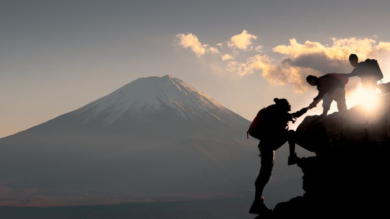 Young asian couple hikers climbing up on the peak of mountain near mountain fuji, Climbing, People helping and team work concept.