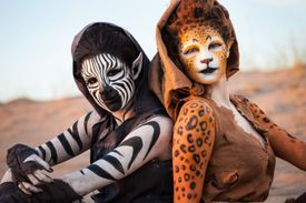 Dos mujeres en el desierto, pintadas al estilo de una cebra y un leopardo.