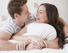 pareja enamorada riendo sobre una cama
