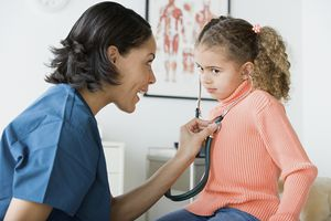 Una médica le está enseñando a una niña a escuchar su corazón con un estetoscopio.
