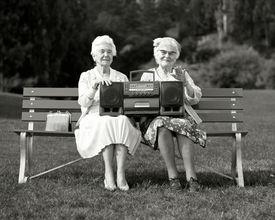 Mujeres que se sientan en banco de parque que sostiene estéreo portátil estéreo