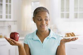 Una mujer sostiene una manzana en una mano y un pedazo de pastel en la otra.