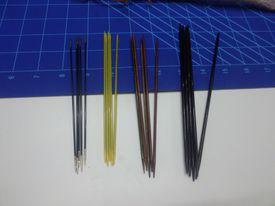 Agujas de dobles puntas de diferentes materiales. De izquierda a derecha, Carbono, plástico y metal, madera laminada y palo de rosa.