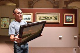 Un miembro del personal del museo verifica el certificado de autenticidad detrás de una pintura