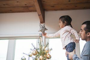 Padre levantando a la niña pequeña poniendo la estrella en el árbol de Navidad