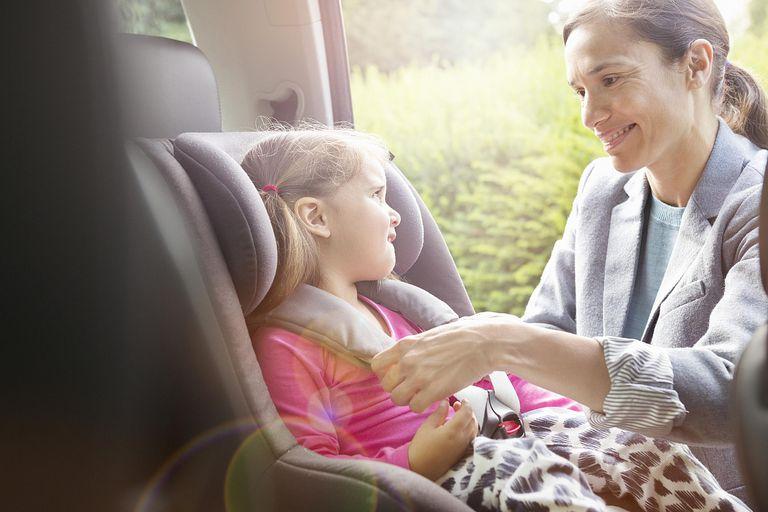Madre poniendo a su hija en una silla de coche